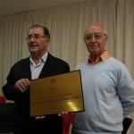 Cesáreo sostiene la placa conmemorativa del homenaje a D. Bernardino. A su lado, Pepe, mira a la cámara.