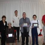 Homenajeados y familiares con sus placas testimoniales, posan junto a la Asociación de Vecinos
