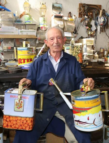Manuel Simón (03/11/2014), sujetando dos regaderas fabricadas por él mismo a partir de latas recicladas