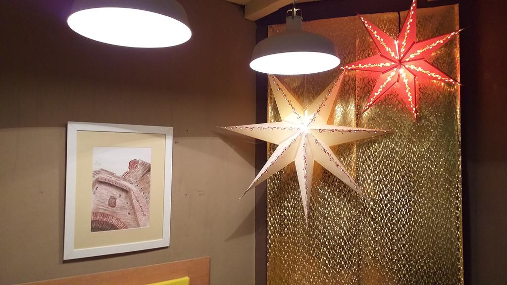 detalle de cuadro de la expo junto a las estrellas navideñas